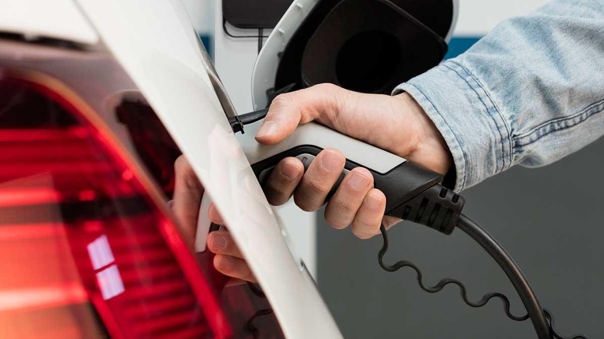 un usuario conecta su vehiculo al cargador